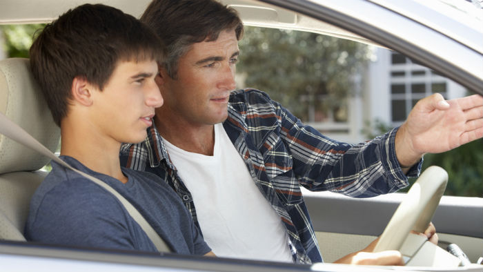Dad teaching son safe driving
