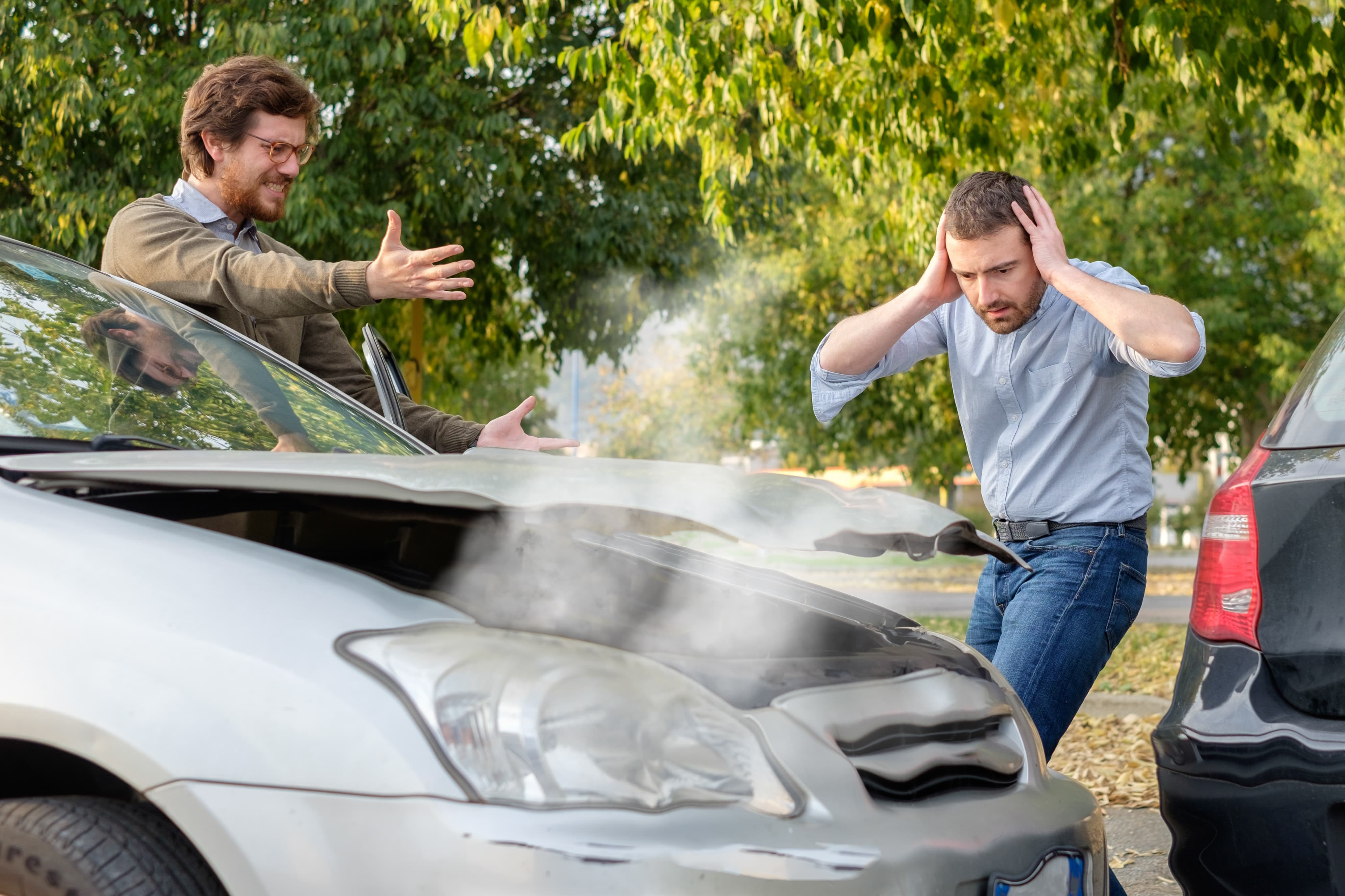 Two men arguing who will pay for car rental after accident.
